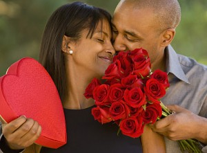 African American man giving Valentine?s Day gifts to wife